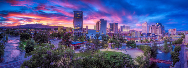 Overview of downtown Reno looking at buildings and river during a purple and orange sunset