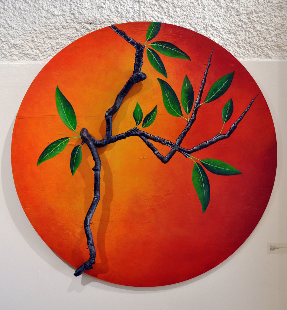 Artwork called tropical sun with tree branch on top of orange circle